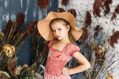Gullig liten flicka i trendig hatt med pioner i studio Royaltyfri Foto