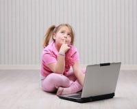 Gullig liten flicka med bärbara datorn royaltyfria foton
