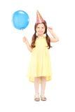 Gullig liten flicka med ballongen för partihattinnehav Arkivbilder