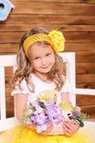 Gullig liten flicka med blommor och vid liv höna royaltyfria bilder