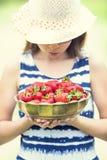 Gullig liten flicka med bunken som är full av nya jordgubbar Pre- tonårig flicka med exponeringsglas och tänder - tand- hänglsen arkivfoton