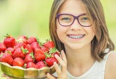 Gullig liten flicka med bunken som är full av nya jordgubbar Pre- tonårig flicka med exponeringsglas och tänder - tand- hänglsen arkivbild
