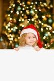 Gullig liten flicka med den röda santa hatten som rymmer det vita brädet med utrymme för text Royaltyfri Foto