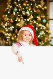 Gullig liten flicka med den röda santa hatten som rymmer det vita brädet och ner pekar Utrymme för text Arkivbild