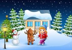 Gullig liten flicka med en hjort framme av det snöig huset i juldag royaltyfri illustrationer