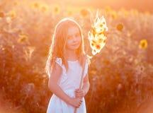 Gullig liten flicka med en väderkvarn Royaltyfria Foton