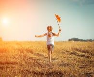 Gullig liten flicka med en väderkvarn Arkivbild