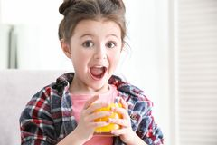 Gullig liten flicka med exponeringsglas av fruktsaft arkivbilder