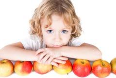 Gullig liten flicka med gruppen av äpplen Arkivfoton