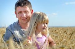 Gullig liten flicka med hennes fader i ett vetefält Royaltyfri Bild