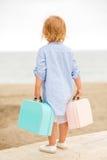 Gullig liten flicka med hennes resväska på havet Arkivfoto