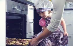 Gullig liten flicka med hennes stekheta kakor för moder i ugn arkivbilder