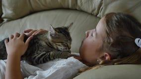 Gullig liten flicka med katten på soffan stock video