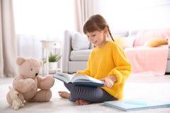 Gullig liten flicka med läseboken för nallebjörn på golv royaltyfria bilder