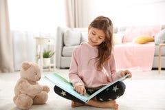 Gullig liten flicka med läseboken för nallebjörn på golv arkivbild
