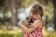 Gullig liten flicka med lite valpen royaltyfri foto