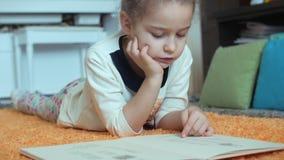 Gullig liten flicka med lockigt hår, i barns pyjamas som ligger på golvet på en stucken matta och själv läsa lager videofilmer