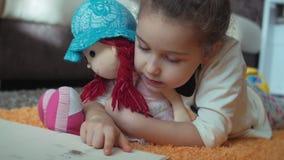 Gullig liten flicka med lockigt hår, i barns pyjamas som ligger på golvet på en stucken matta och själv läsa arkivfilmer