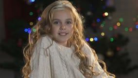 Gullig liten flicka med lockigt hår som ler och poserar på kameran, julhelgdagsafton arkivfilmer