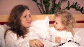 Gullig liten flicka med lockigt hår som sover omfamning med modern i vit säng stock video