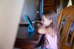 Gullig liten flicka med minnestavladatoren inomhus Arkivfoton