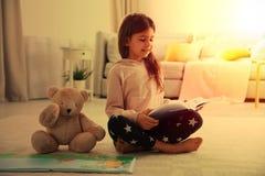 Gullig liten flicka med nallebjörnen som sitter på golv och läseboken arkivfoto