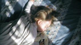Gullig liten flicka med sömnar för blont hår på sängen på hennes mage som tänds av solskenet med en nallekanin stock video