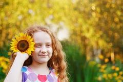 Gullig liten flicka med solrosor i hennes lockiga rödhårig manhår, enj Arkivbild