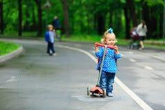 Gullig liten flicka med sparkcykeln i parkera Royaltyfria Bilder