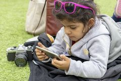 Gullig liten flicka med sunglass som kontrollerar hennes smartphone medan res royaltyfri bild