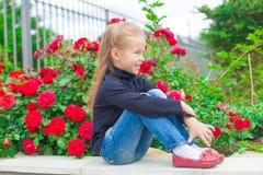 Gullig liten flicka nära blommorna i gård av henne Royaltyfria Foton