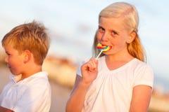 Gullig liten flicka och broder Enjoying Their Lollipops royaltyfria foton