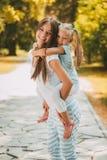 Gullig liten flicka och hennes mamma royaltyfria foton