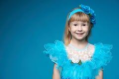 Gullig liten flicka på blå bakgrund Arkivfoton