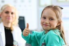 Gullig liten flicka på doktorskontoret som visar respekt och tacksamhet fotografering för bildbyråer