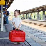 Gullig liten flicka på en järnvägsstation Arkivbild