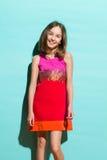 Gullig liten flicka på en turkosbakgrund Fotografering för Bildbyråer