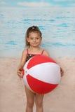 Gullig liten flicka på stranden med bollen Royaltyfria Foton