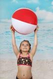Gullig liten flicka på stranden med bollen Arkivbilder