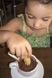 Gullig liten flicka som äter churros med varm choklad Arkivfoton