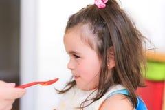 Gullig liten flicka som äter puré arkivbild