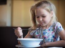 Gullig liten flicka som äter soppa i restaurangen Arkivfoto