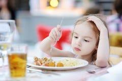 Gullig liten flicka som äter spagetti Fotografering för Bildbyråer