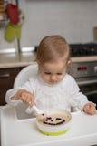 Gullig liten flicka som äter sund havregröt Arkivfoton