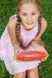 Gullig liten flicka som äter vattenmelon på gräset i sommartid med långt hår för hästsvans och toothy leendesammanträde på gräs o Royaltyfri Foto