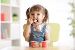 Gullig liten flicka som äter yoghurt arkivfoton