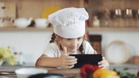 Gullig liten flicka som använder smartphonen under frukosten som sitter på köket Hon är iklädd ett förkläde som ser arkivfilmer