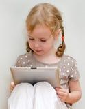 Gullig liten flicka som använder tabletdatoren arkivbilder