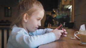 Gullig liten flicka som anv?nder p? den smarta telefonen p? kaf?t Lyckligt barn som har gyckel och kopplar av efter skola Naturli arkivfilmer