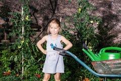 Gullig liten flicka som arbeta i trädgården i trädgården Royaltyfria Bilder
